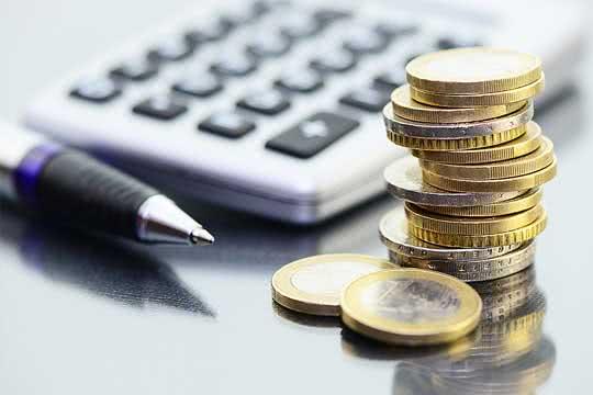 Geldanlage - Taschenrechner mit EURO-Münzen im Vordergrund