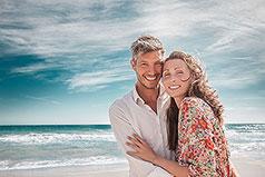 Paar mittleren Alters am Strand lächelt in die Kamera