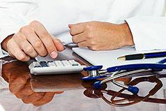 Hände eines Arztes tippen Zahlen in einen Tischtaschenrechner