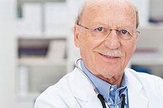 Älterer Arzt lächelt in Kamera