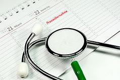 Kalender mit Termin für Praxisübernahme und Stethoskop im Vordergrund