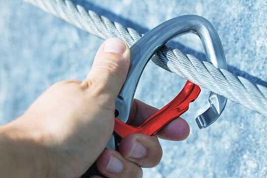 Vorsorge - Nahaufnahme einer Hand, die einen Karabiner in ein Stahlseil einklinkt