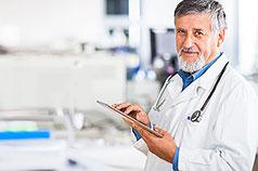 Älterer Arzt mit Tablet-PC lächelt in Kamera