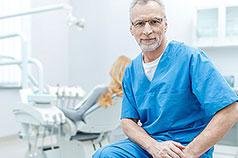Älterer Zahnarzt mit Patientin im Hintergrund lächelt in Kamera
